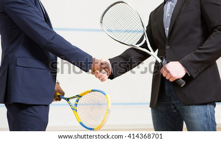 Two businessmen shaking hands before playing squash on court. Sporty men holding rackets on squash court. - stock photo