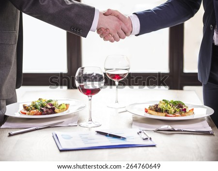 Two businessmen shaking hands during a business lunch. Business meeting. - stock photo