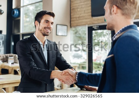 Two businessmen shaking hands in a cafe - stock photo