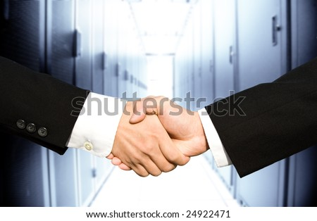 Two businessmen shaking hands in a technology data center