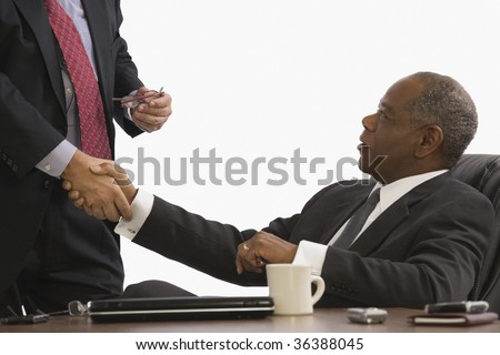 Two businessmen shaking hands in an office