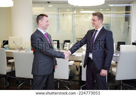 Two businessmen shaking hands in conference hall - stock photo