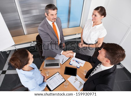 Two Businessmen Shaking Hands In Front Of Colleagues At Office - stock photo
