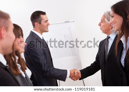 Two businessmen shaking hands in greeting and congratulations during an introductory line up of young staff in an office - stock photo