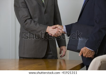 Two businessmen shaking hands in meeting room. - stock photo