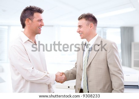 Two businessmen shaking hands in office, smiling. - stock photo