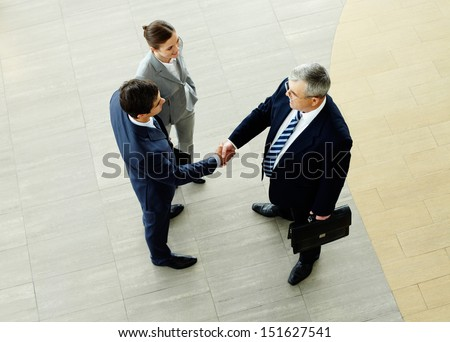 Two businessmen shaking hands indicating successfully made deal - stock photo
