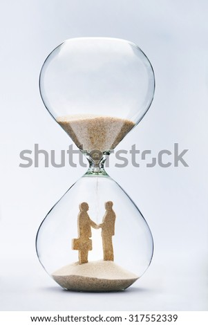 Two businessmen shaking hands made out of falling sand inside hourglass - stock photo