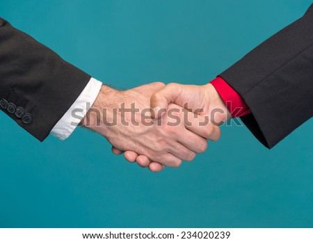Two businessmen shaking hands on a blue background - stock photo