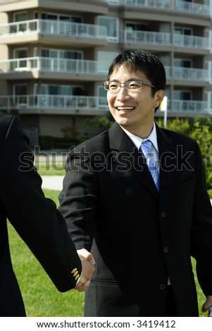 Two businessmen shaking hands on a deal - stock photo