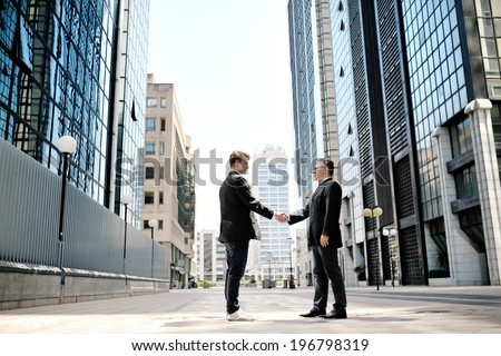 two businessmen shaking hands on background modern office corporate buildings - stock photo