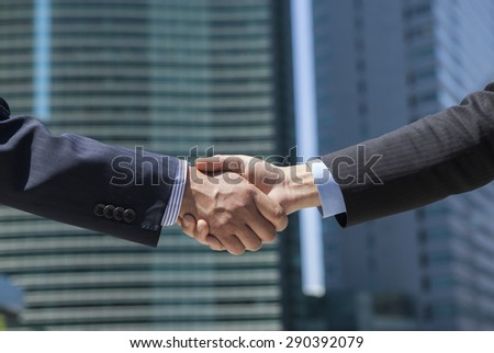 Two businessmen shaking hands on the street - stock photo