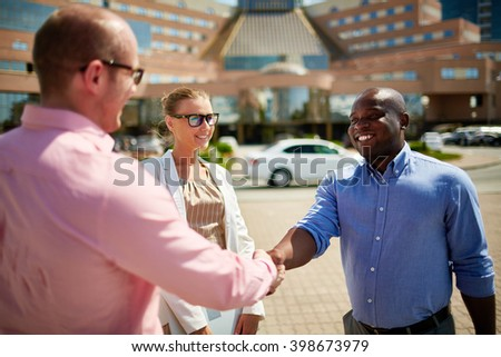 Two businessmen shaking hands outdoors - stock photo
