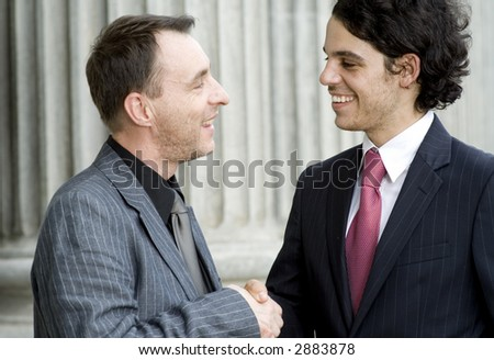 Two businessmen shaking hands outside in front of a building