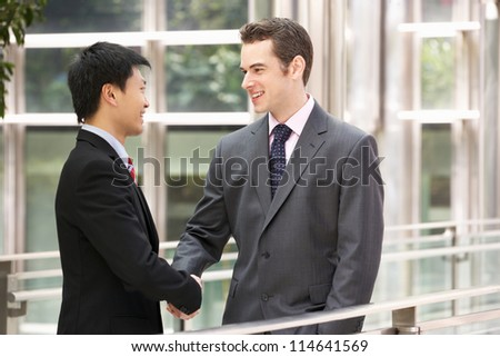 Two Businessmen Shaking Hands Outside Office - stock photo