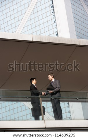 Two Businessmen Shaking Hands Outside Office Building - stock photo