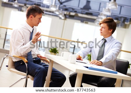 Two businessmen sitting at table and discussing strategy