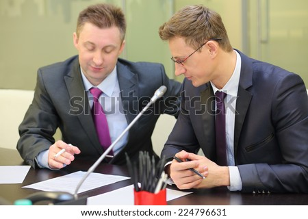 Two businessmen sitting at the table with documents in conference hall - stock photo