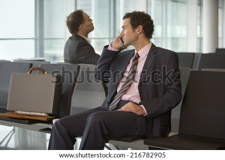Two businessmen sitting in the airport.