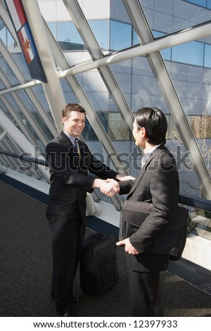 Two businessmen smiling and shaking hands in an office lobby - stock photo