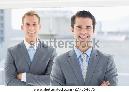 Two businessmen smiling at camera in the office