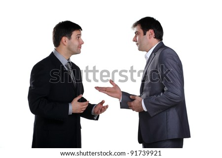 Two businessmen standing and talking with one of them having expression on his face - stock photo