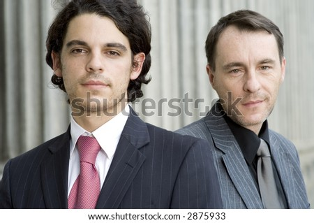 Two businessmen standing in front of an old building