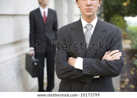 two businessmen standing in front of building wearing suits looking at camera - stock photo