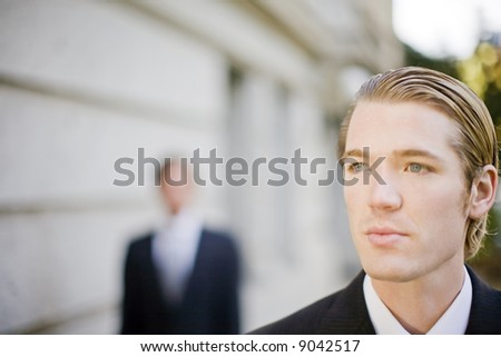 two businessmen standing in front of building wearing suits looking past camera - stock photo
