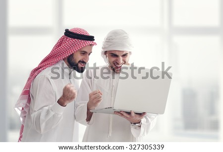 Two businessmen standing in office holding laptop and feeling happy / Success Concept - stock photo