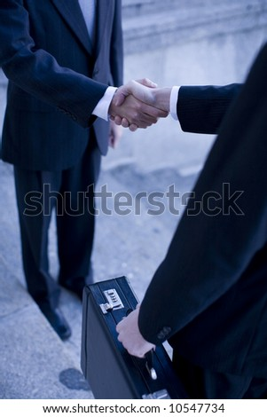 two businessmen standing shaking hands on steps - stock photo