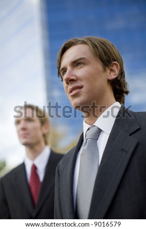 two businessmen standing side by side looking forward in front of tall blue office building - stock photo