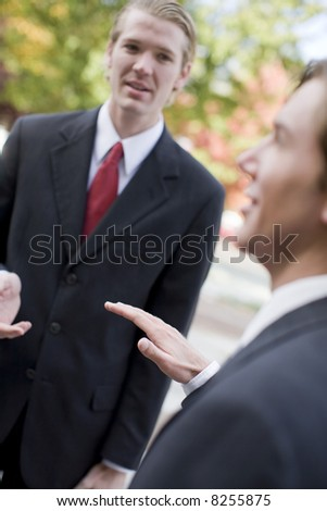 two businessmen standing talking outdoors