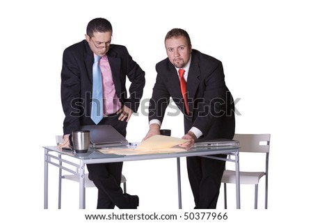 Two Businessmen Standing Up on their Desk  in an Office Working