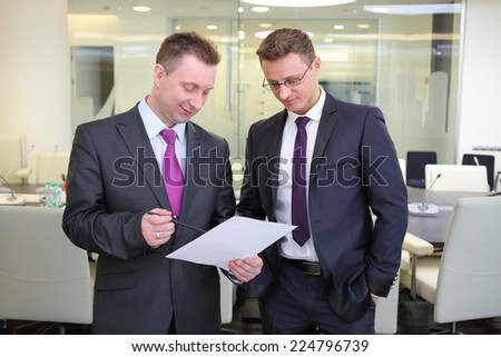 Two businessmen standing with a blank sheet of paper in conference hall - stock photo