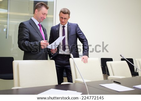 Two businessmen standing with a blank sheet of paper near conference table - stock photo