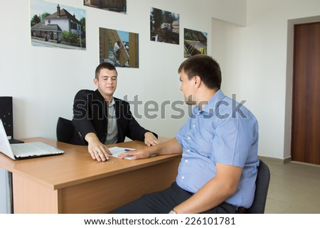 Two Businessmen Talking about Real Estate at the Table Area of the Agent at the Office. - stock photo