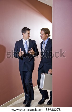 Two businessmen talking and walking down office corridor - stock photo