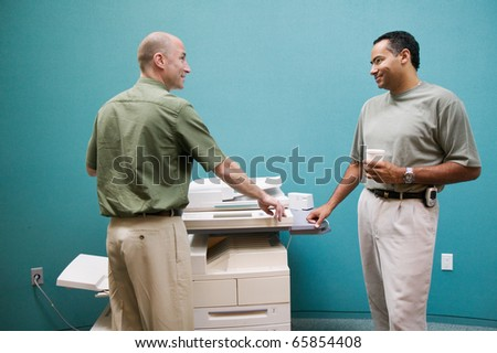 Two businessmen talking at copy machine - stock photo