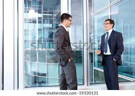 Two businessmen talking in office - stock photo