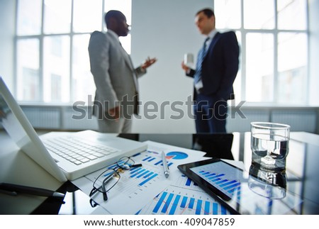 Two businessmen talking in office at table with laptop, touchpad and financial documents - stock photo