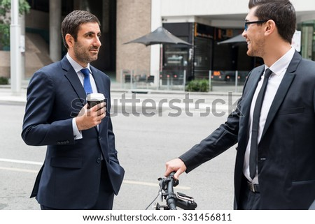 Two businessmen talking outdoors while taking coffee break