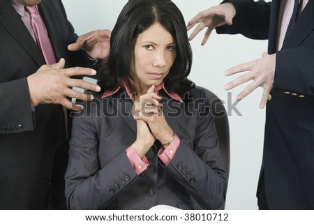 Two businessmen threatening a businesswoman with harassment. - stock photo