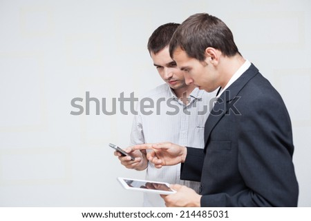 Two businessmen using digital tablet and smartphone.