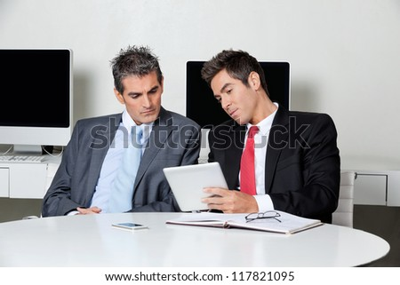 Two businessmen using digital tablet at desk in office - stock photo