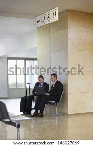 Two businessmen using laptop in the airport lobby - stock photo