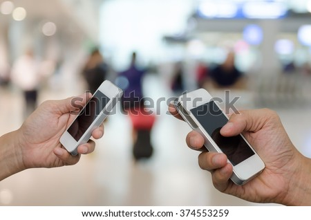Two businessmen using mobile smart phone with blurred peoples at airport, communication concept, transfer concept. - stock photo