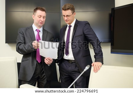 Two businessmen view documents standing with a blank sheet of paper near conference table