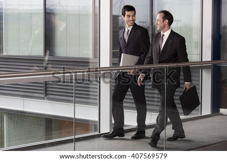 Two businessmen walking along in modern office building - stock photo