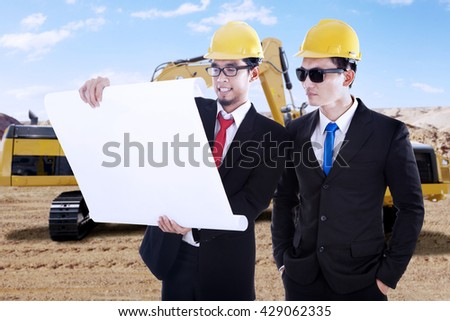 Two businessmen wearing business suit and look at blueprint in the construction sites - stock photo